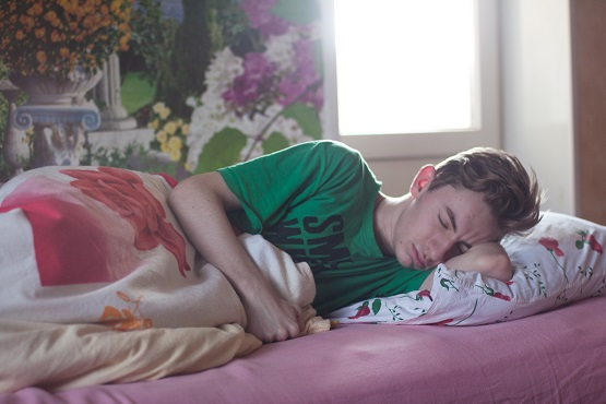 A teenage boy sleeping in bed