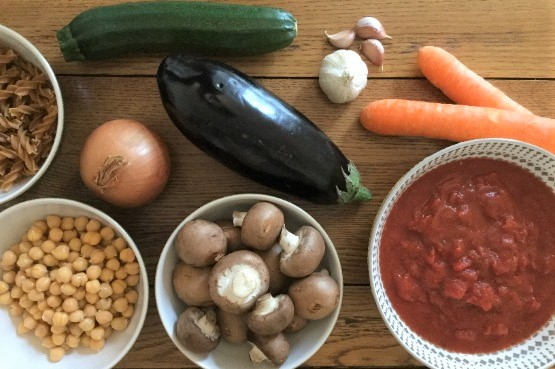 vegetables and bowls of tomato sauce, mushrooms, chickpeas and pasta