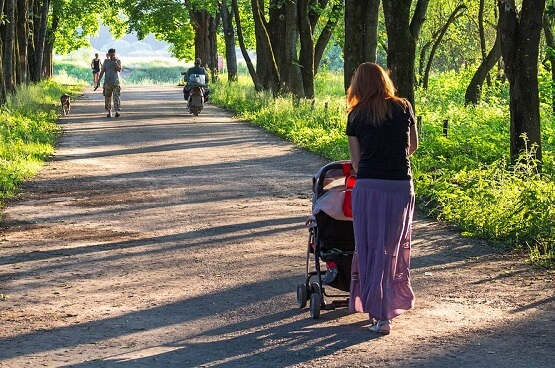 Woman pushing pram outdoors