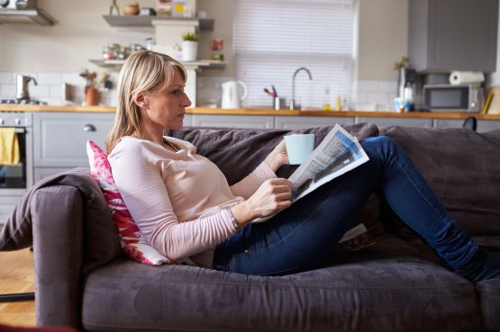 woman relaxing on sofa with a drink and book in hand