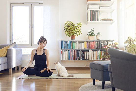 Woman sitting on a yoga mat with her cat