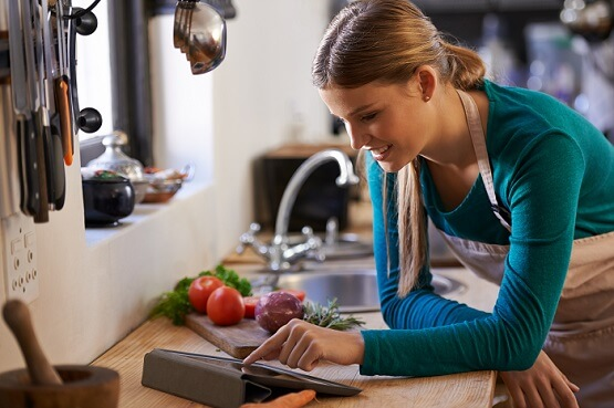 woman in a kitchen looking at a recipe on a tablet