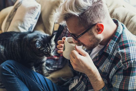 A man sitting on a sofa with his cat, drinking coffee