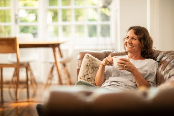 A woman relaxing with a cup of coffee on a sofa