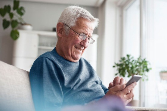 An elderly man looking at his phone
