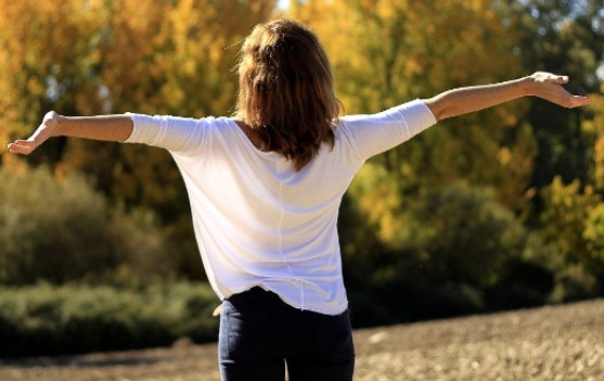 a woman standing outdoors with arms stretched