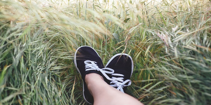 An image of crossed feet in the grass