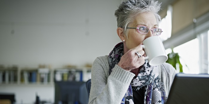 A senior woman is having a cup of tea