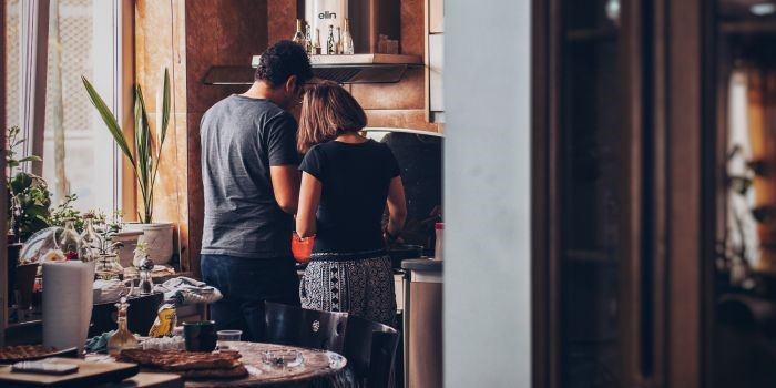 a man and a woman cooking in the kitchen