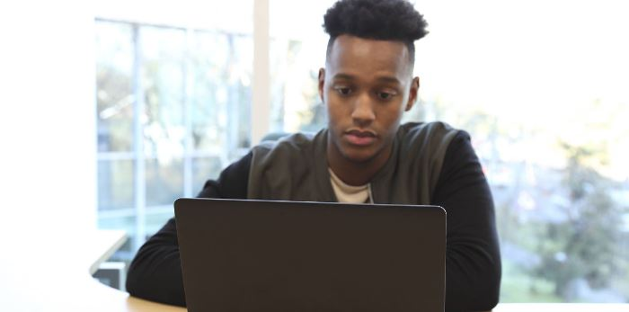 A teenage boy is on laptop
