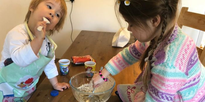 Two young children baking together