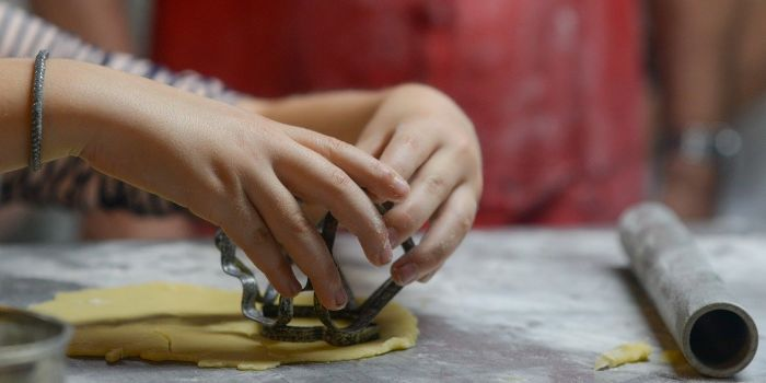 a child cutting shapes on a pastry sheet
