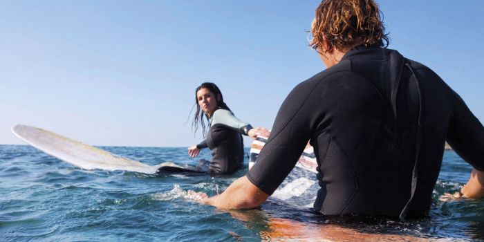 A man and a woman on surfboards