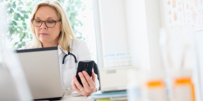 female doctor on a phone and laptop