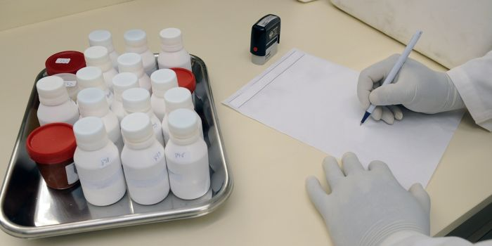 person in gloves writing prescription, next to tray of medicines