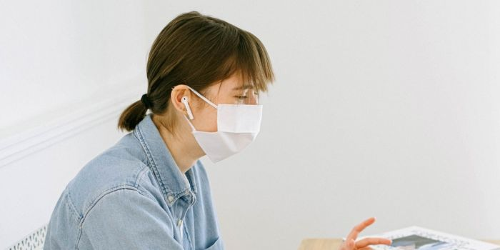 a woman with a face mask at her desk