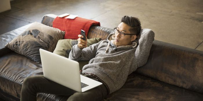 man on a sofa with a mobile in hand and a laptop on his lap