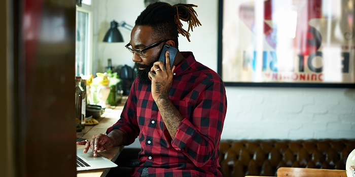 man with a checked shirt on a phone and laptop