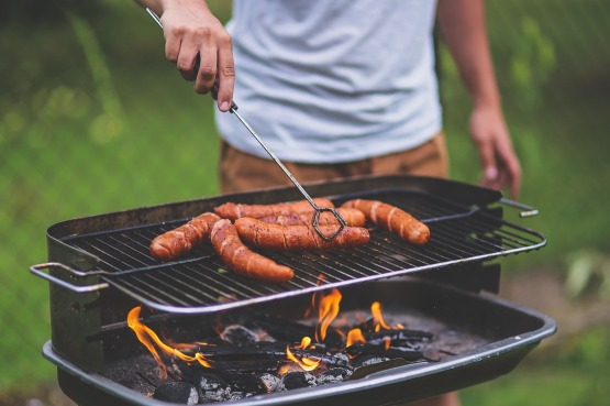 Picture of a man cooking sausages on the barbeque