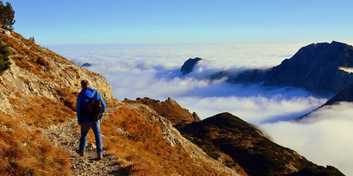 A man walking in the moutnains above the clouds