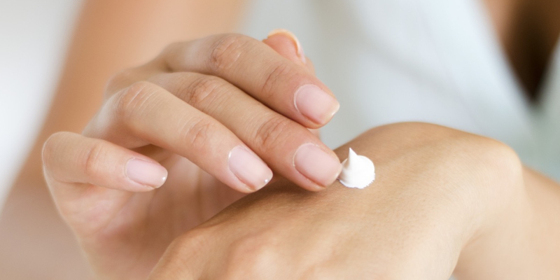 Image of a woman's hands, applying moisturiser