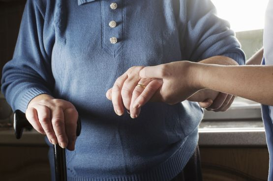 A carer helps an elderly lady with a walking stick