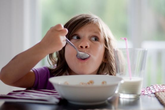 Young eats her breakfast with a glass of milk