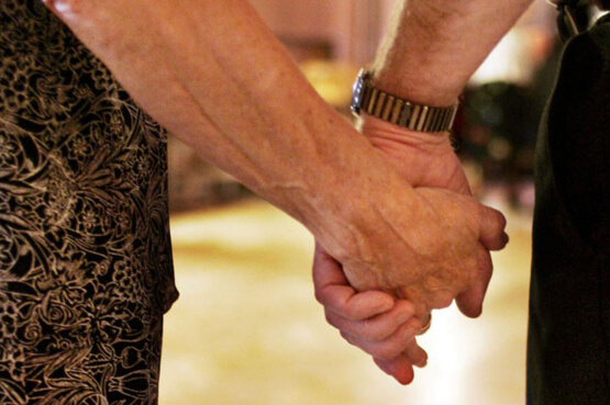 Close-up image of an older couple holding hands