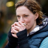 A woman sipping a hot drink