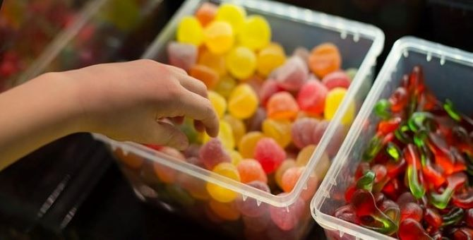 Child's hand reaching for sweets in a bowl