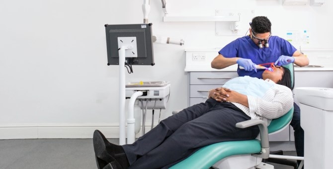A dental patient sat back in a chair being treated by a dentist