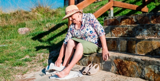 Senior woman sitting on stairs wiping sand off her feet