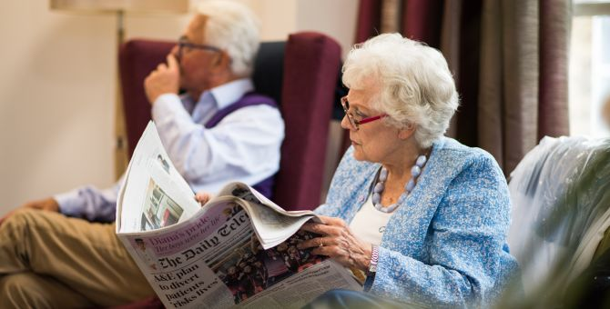 An older lady is reading a newspaper