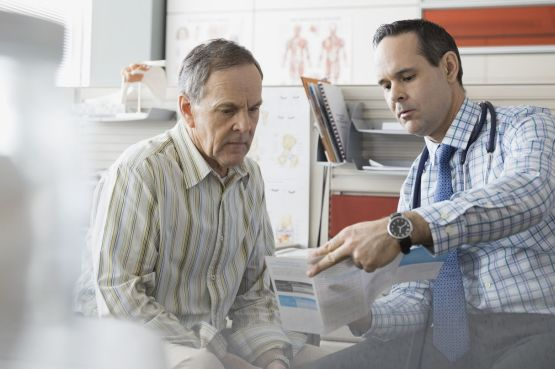 A doctor showing a senior patient a leaflet in his office